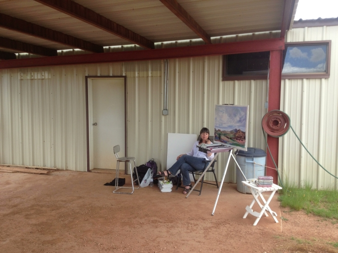 Painting on location, en plein air, means weathering whatever comes your way. Here, I've hurriedly moved my easel and supplies beneath a nearby shelter as the storm I was painting  started pelleting me with hailstones! Lindy Cook Severns, Fort Davis, TX